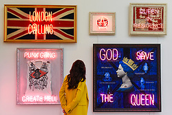 © Licensed to London News Pictures. 25/09/2019. LONDON, UK. A staff member views neon works by Illuminati Neon, combining vintage flags and neon, at the preview of START, a contemporary art fair comprising eclectic works from a variety of international emerging artists.  The fair takes place at the Saatchi Gallery in Chelsea 26 to 29 September 2019.  Photo credit: Stephen Chung/LNP