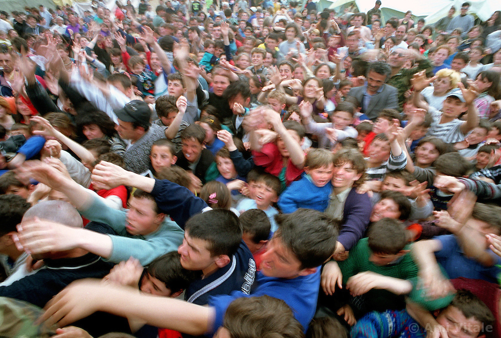 Ethnic Albanian refugees from Kosovo rush to get goods from the Italian Nato forces in the Stenkovec camo near Skopje, Macedonia, April 10, 1999.  (Photo By Ami Vitale)