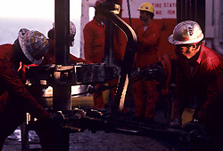 Stock photo of three men working on an oil rig