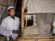 07 NOVEMBER 2014 - SITTWE, RAKHINE, MYANMAR: A Rohingya Muslim man in the doorway of his tent in an IDP camp for Rohingya. After sectarian violence devastated Rohingya communities and left hundreds of Rohingya dead in 2012, the government of Myanmar forced more than 140,000 Rohingya Muslims who used to live in and around Sittwe, Myanmar, into squalid Internal Displaced Persons camps. The government says the Rohingya are not Burmese citizens, that they are illegal immigrants from Bangladesh. The Bangladesh government says the Rohingya are Burmese and the Rohingya insist that they have lived in Burma for generations. The camps are about 20 minutes from Sittwe but the Rohingya who live in the camps are not allowed to leave without government permission. They are not allowed to work outside the camps, they are not allowed to go to Sittwe to use the hospital, go to school or do business. The camps have no electricity. Water is delivered through community wells. There are small schools funded by NOGs in the camps and a few private clinics but medical care is costly and not reliable.   PHOTO BY JACK KURTZ