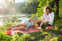 Couple on picnic using tablet with watermelon by river, Bavaria, Germany
