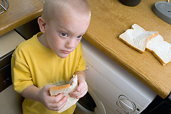 Young boy eating a slice of white bread in the kitchen at home,