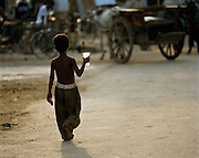 Young boy with a cup walking in street, Lucknow, Uttar Pradesh, India