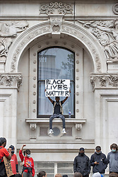 © Licensed to London News Pictures. 03/06/2020. London, UK. A Black Lives Matter protester sits on the window of the Foreign Office in Whitehall during a demonstration following the death of African American George Floyd while in police custody. The death of George Floyd, who died after being restrained by a police officer In Minneapolis, Minnesota, has caused widespread rioting and looting across the USA. Photo credit: Peter Macdiarmid/LNP