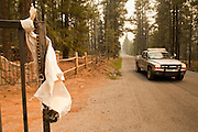 """05 JUNE 2011 - GREER, AZ:  A sheriff's vehicle passes an empty residence in Greer Sunday. Officials have asked residents to tie white towels to their doors and gates so officials know the residence is empty. The fire grew to more than 180,000 acres by Sunday with zero containment. A """"Type I"""" incident command team has taken command of the fire.    PHOTO BY JACK KURTZ"""