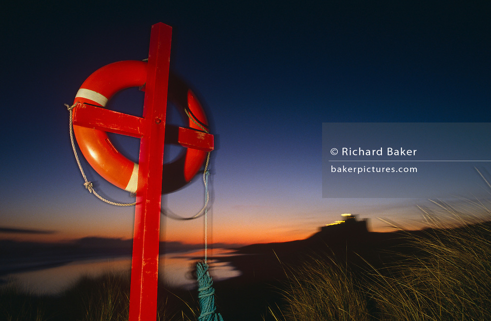 A life belt hangs on a cross-shaped post, all painted a vivid red as the sun sinks down below the horizon and beyond the historic Bamburgh Castle, in Northumberland, northern England. Lit with a strong off-camera flash we see the slightly blurred device, invented for saving lives at sea, with a ghostly corona around its form, against a fading blue sky. The rope dangles near the ground, around which the grasses of the dunes blow in a faint breeze. Only the foreground is lit by the flash and the distant castle building and shoreline. We see such equipment and imagine safety and rescue and also jeopardy and hazards at sea. Supplied for those taking risks and making stupid decisions makes these items essential on coastal areas.