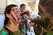 Female Israeli soldier has her face painted by a fellow soldier. Photography by Debbie Zimelman, Modiin, Israel