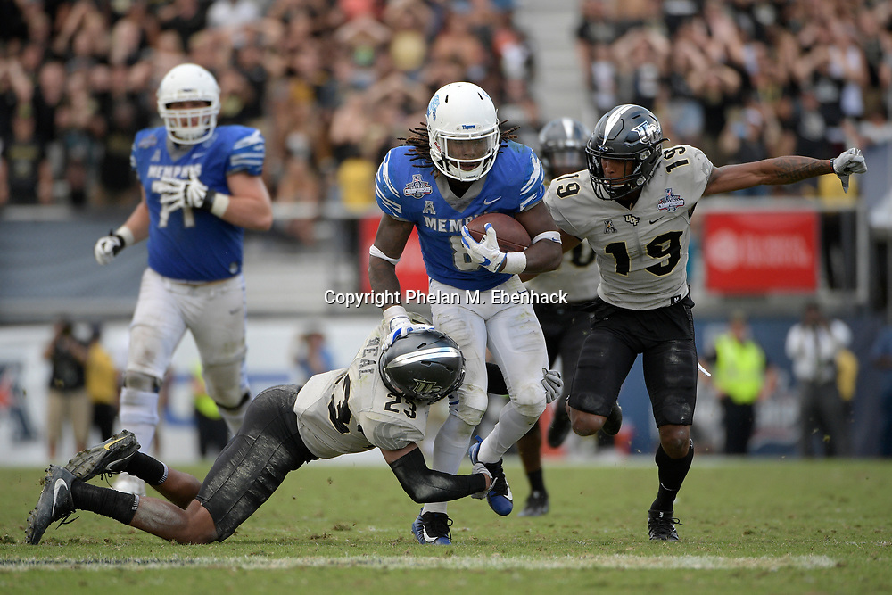 Memphis running back Darrell Henderson (8) is tackled by Central Florida defensive back Tre Neal (23) and defensive back Mike Hughes (19) after rushing for yardage during the second half of the American Athletic Conference championship NCAA college football game Saturday, Dec. 2, 2017, in Orlando, Fla. Central Florida won 62-55. (Photo by Phelan M. Ebenhack)