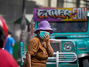 30 JANUARY 2018 - GUINOBATAN, ALBAY, PHILIPPINES: A woman covers her mouth and nose while she crosses a street in Guinobatan during an ash fall. Mayon volcano continued to erupt but not as dramatically as it did last week. The small eruptions are still sending ash clouds over communities west of the volcano and the government is encouraging people to stay indoors, wear face masks and avoid strenuous activities when ash is falling.     PHOTO BY JACK KURTZ