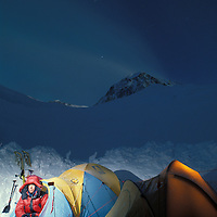 USA, Alaska, Denali National Park, (MR) Photographer Paul Souders in tent at twilight on Kahiltna Glacier on Mount McKinley