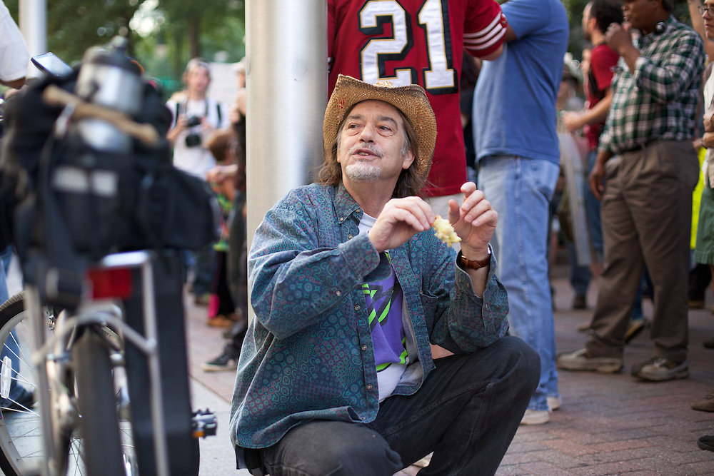 A man squats to eat an apple as the protest in front of BOA headquarters gets ready continue on.
