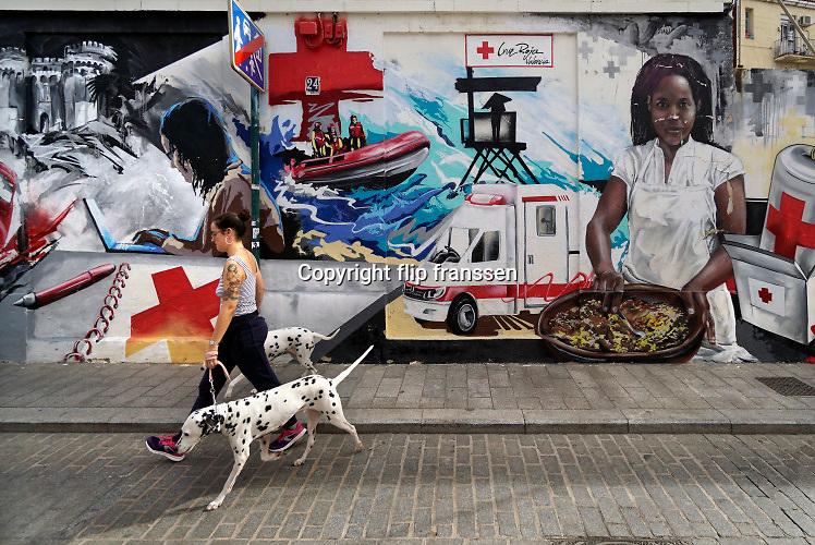 Spanje, Valencia, 3-11 2019  Graffiti, muurschildering  bij het gebouw van het lokale spaanse  rode kruis in het centrum, stadscentrum, van de stad . Een vrouw die haar honden uitlaat loopt voorbij .Foto: Flip Franssen
