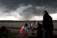 Storm chasers Tim Marshall (crouching, right) and Lindsay Bennett (crouching, left) deploy a probe in front of a rapidly advancing tornado in Goshen County, Wyoming, USA, June 5, 2009.  Both are participating in Project Vortex 2.  Project Vortex 2 is a two year National Science Foundation and NOAA funded science mission to study tornadoes and supercell thunderstorms.
