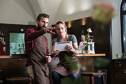 Young restaurant owners discussing while sitting by bar counter