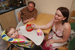 Mother feeding her baby in kitchen