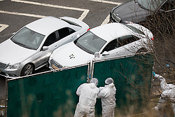 © Licensed to London News Pictures. 03/01/2017. Huddersfield, UK. Forensic scenes of crime officers erect a screen to block the view of a bullet riddled silver Audi car at the slip road at Junction 24 of the M62 motorway in Huddersfield . West Yorkshire police have announced a man has died following the discharge of a police firearm , during what they describe as a pre-planned operation , yesterday evening (2nd January 2017) . Photo credit : Joel Goodman/LNP