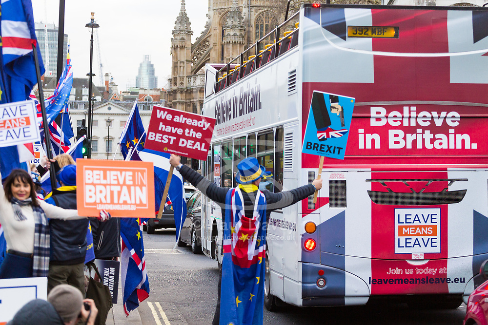 As a Leave Means Leave bus pass the Houses of Parliament SODEM's Steve Bray defiantly waves his Remain placards. London, January 14 2019.
