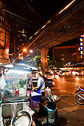 Street food vendor with Skytrain overhead.