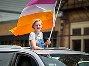 """28 JUNE 2020 - DES MOINES, IOWA: A person with a Pride Flag in the moon roof of a car during the Capitol City Pride Parade in Des Moines. Most of the Pride Month events in Des Moines were cancelled this year because of the COVID-19 pandemic, but members of the Des Moines LGBTQI community, and Capitol City Pride, the organization that coordinates Pride Month events, organized a community """"parade"""" of people driving through the East Village of Des Moines displaying gay pride banners and flags. About 75 cars participated in the parade.     PHOTO BY JACK KURTZ"""