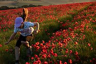A young girl runs through a field of poppies near Goodwood, West Sussex.<br /> Picture date Thursday 24th June, 2021.<br /> Picture by Christopher Ison. Contact +447544 044177 chris@christopherison.com
