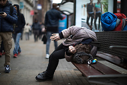 © Licensed to London News Pictures . 06/04/2017 . Manchester , UK . A man with a pipe in his hand lies slumped on a bench in front of Morrisons Supermarket in Piccadilly Gardens . An epidemic of abuse of the drug spice by some of Manchester's homeless population , in plain sight , is causing users to experience psychosis and a zombie-like state and is daily being witnessed in the Piccadilly Gardens area of Manchester , drawing large resource from paramedic services in the city centre . Photo credit : Joel Goodman/LNP
