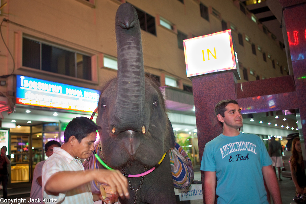 """Mar. 25, 2009 -- BANGKOK, THAILAND: Tourists pose for photos with a young elephant at the entrance to the Nana Entertainment Plaza on Soi Nana in Bangkok, Thailand. It has been illegal to bring elephants into Bangkok for about 10 years but police look the other way when the giants animals are brought into the """"entertainment"""" districts, which are also the city's red light districts.  Photo by Jack Kurtz"""