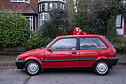 Classic Austin Mini Metro car tied up with a red bow on a street in Moseley as a gift for Christmas Day on 25th December 2020 in Birmingham, United Kingdom. The Metro is a supermini car, later a city car that was produced by British Leyland BL and, later, the Rover Group from 1980 to 1998. It was launched in 1980 as the Austin Mini Metro. It was intended to complement and eventually replace the Mini, and was developed under the codename LC8. The Metro was named by What Car? as Car of The Year in 1983 as an MG, and again as a Rover in 1991.