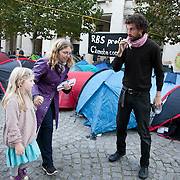 A mother and daughter ar emaking their way through the camp as a man is brushing his teeth. Day three of the occupation - and the first Monday.  The Occupy London Stock Exchange movement was formed in London in solidarity with the US based Occupy Wall Street. The movements are a respons and in anger to what is seen by many as corporate greed and a failed banking system being bailed out by the public, - which in return are suffering austerity measures to make up for the billions of lost money. The movement occupied the St Paul's Square in the City of London Sat Oct 15 after it failed to secure and occupy Pator Noster Square and the Stock Exchnage itself.