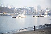 Man walking along the riverfront beach at low tide on the River Thames with his metal detector, searching for artifacts. The South Bank is a significant arts and entertainment district, and home to an endless list of activities for Londoners, visitors and tourists alike.