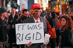 "© Licensed to London News Pictures. 09/11/2016. New York City, USA. A man dressed as Donald Trump holds a sign reading ""IT WAS RIGGED"" while watching election coverage in Times Square, New York City, on Wednesday, 9 November. Photo credit: Tolga Akmen/LNP"