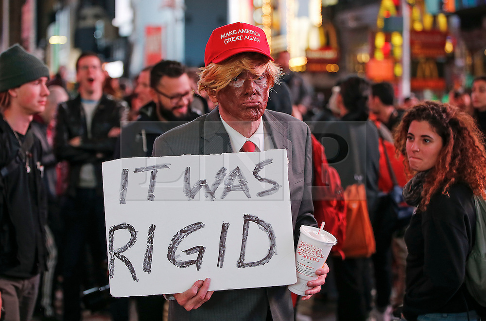 """© Licensed to London News Pictures. 09/11/2016. New York City, USA. A man dressed as Donald Trump holds a sign reading """"IT WAS RIGGED"""" while watching election coverage in Times Square, New York City, on Wednesday, 9 November. Photo credit: Tolga Akmen/LNP"""