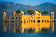 """Jal Mahal (meaning """"Water Palace"""") is a palace located in the middle of the Man Sagar Lake in Jaipur city, the capital of the state of Rajasthan, India. The palace and the lake around it were renovated and enlarged in the 18th century by Maharaja Jai Singh II of Amber. The Jal Mahal palace has got an eye-popping makeover. Traditional boat-makers from Vrindavan have crafted the Rajput style wooden boats. A gentle splashing of oars on the clear lake waters takes you to Jal Mahal. You move past decorated hallways and chambers on the first floor to climb all the way up to the fragrant Chameli Bagh. Across the lake, you can view the Aravalli hills, dotted with temples and ancient forts, and on the other side, bustling Jaipur. The most remarkable change is in the lake itself. The drains were diverted, two million tonnes of toxic silt were dredged from the bottom, increasing its depth by over a metre, a water treatment system was developed, local vegetation and fish reintroduced, the surrounding wetlands regenerated and five nesting islands created to attract migratory birds."""