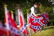 A Confederate re-enactor places Confederate flags on tombs of soldiers killed during the US Civil War at Magnolia Cemetery to mark Confederate Memorial Day on May 10, 2011 in Charleston, South Carolina.  South Carolina is one of three states that marks the day as a public holiday.
