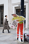 A passer-by walks near a construction industry warning sign, erected to warn pedestrians, but damaged so that it is seemingly bending over at the waist, on 8th March 2021, in London, England.
