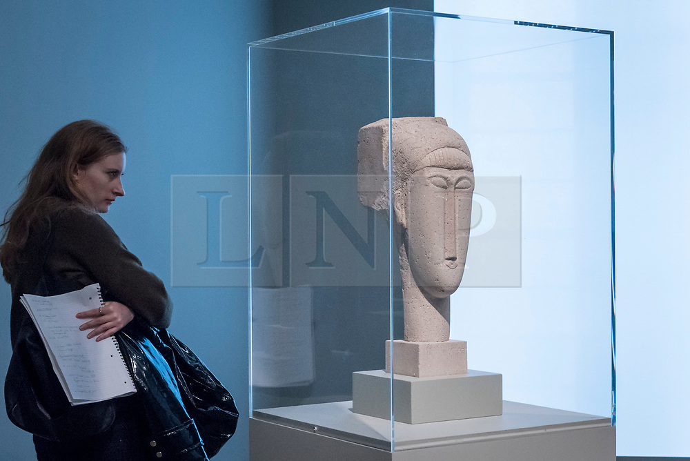"""© Licensed to London News Pictures. 21/11/2017. London, UK.  A visitor views one of several """"Head"""" sculptures.  """"Preview of """"Modigliani"""", the most comprehensive exhibition of works by Amedeo Modigliani ever held in the UK.  On display are iconic portraits, sculptures and 12 nudes, the largest group ever shown in the UK.  The show runs 23 November to 2 April 2018.  Photo credit: Stephen Chung/LNP"""