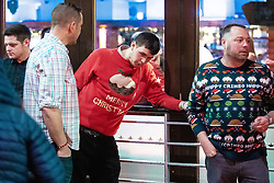 """© Licensed to London News Pictures . 21/12/2018 . Manchester , UK . A man wearing a Merry Christmas sweater vomits and slumps back against a window at the Printworks . Revellers out in Manchester City Centre overnight during """" Mad Friday """" , named for historically being one of the busiest nights of the year for the emergency services in the UK . Photo credit : Joel Goodman/LNP"""