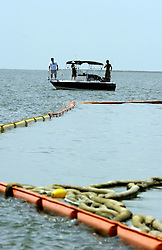23 July 2010. Cat Islands. Barataria Bay near Grand Isle, Louisiana. <br /> Despite a 65 yard (20 meter) exclusion zone around oil boom without special permission from the Joint Information Center, (max fine $40,000 and class 'D' felony) local fishermen have returned to the area recently opened to recreational fishing. Commercial fishing is still closed. Local fishermen are greatly relieved to be back on the water catching speckled trout, redfish, halibut and many other species as pelicans look on from oil boom.<br /> But has mother nature naturally cleaned up the oil spill with human help?  In what would appear to be good news for the area, the pelicans and boom are relatively clean and fish tested by every level of food safety is classified fit for human consumption. A sweep through Barataria bay uncovered only two oiled pelicans. No tar balls or oil were seen in the water. Many of the marsh grasses appeared to be growing back. Perhaps the area is witnessing the beginning of the end of the disaster from BP's massive oil spill in the Gulf of Mexico? It will be many years before the long term effects of the spill are known and a tropical storm or hurricane could still bring large slicks of oil ashore. For now though, the situation looks relatively good.<br /> Photo credit; Charlie Varley/varleypix.com