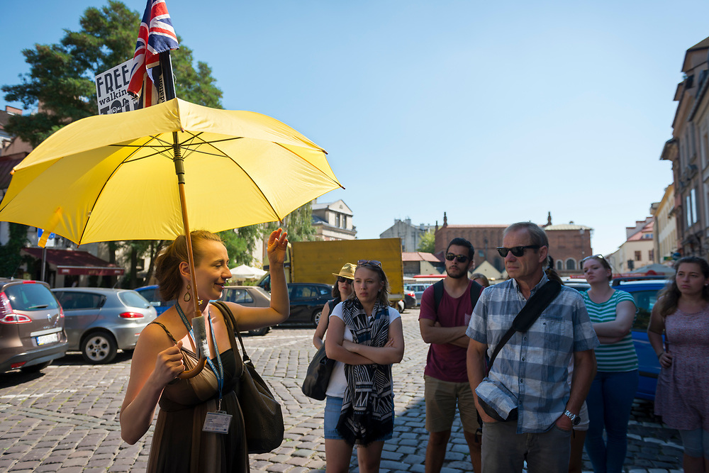 A guide holds a yellow umbrella with a British flag during a free walking tour in the Kazimierz Jewish quarter in Krakow, Poland (August 26, 2016)