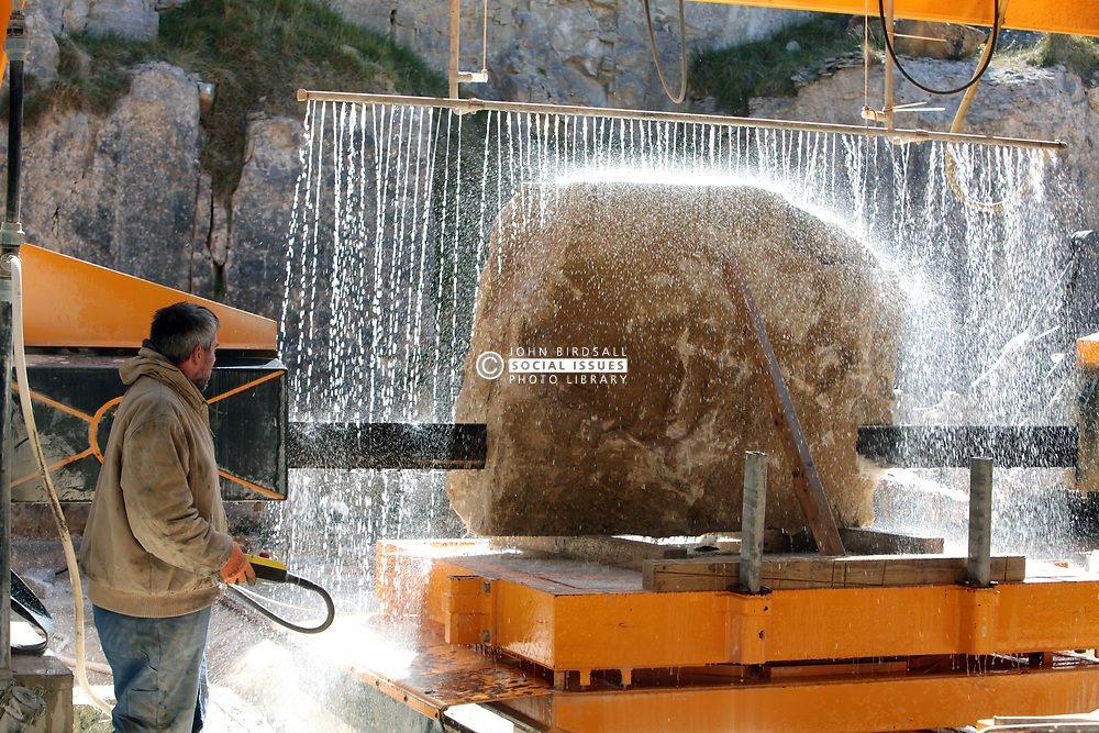 Covid 19 - Stonemason Justin Warren cuts a recently quarried purbeck stone slab in preparation for creating the many new headstones required as a consequence of the mounting Coronavirus death toll, one of an increasing daily number (9 that day) being ordered from a Purbeck stone quarry at St Aldhelm's head Dorset UK April 2020