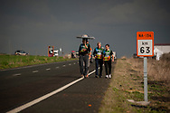 """People walk by the road as they go to the point they will wait for the 20th Korrika. Lodosa (Basque Country). March 31, 2017. The """"Korrika"""" is a relay course, with a wooden baton that passes from hand to hand without interruption, organised every two years in a bid to promote the basque language. The Korrika runs over 11 days and 10 nights, crossing many Basque villages and cities. This year was the 20th edition and run more than 2500 Kilometres. Some people consider it an honour to carry the baton with the symbol of the Basques, """"buying"""" kilometres to support Basque language teaching. (Gari Garaialde / Bostok Photo)"""