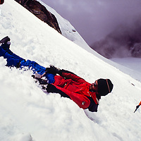 Mountain guide John Fischer demonstrates  ice ax arrest techniques on the Dzongla Glacier at an early mountaineering school for sherpas in the Khumbu region of Nepal, 1980.