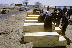 Hart Island, NYC, location of former US missile base and site of Potters field burial plots. Inmates from Rikers Island prepare wooden coffins.