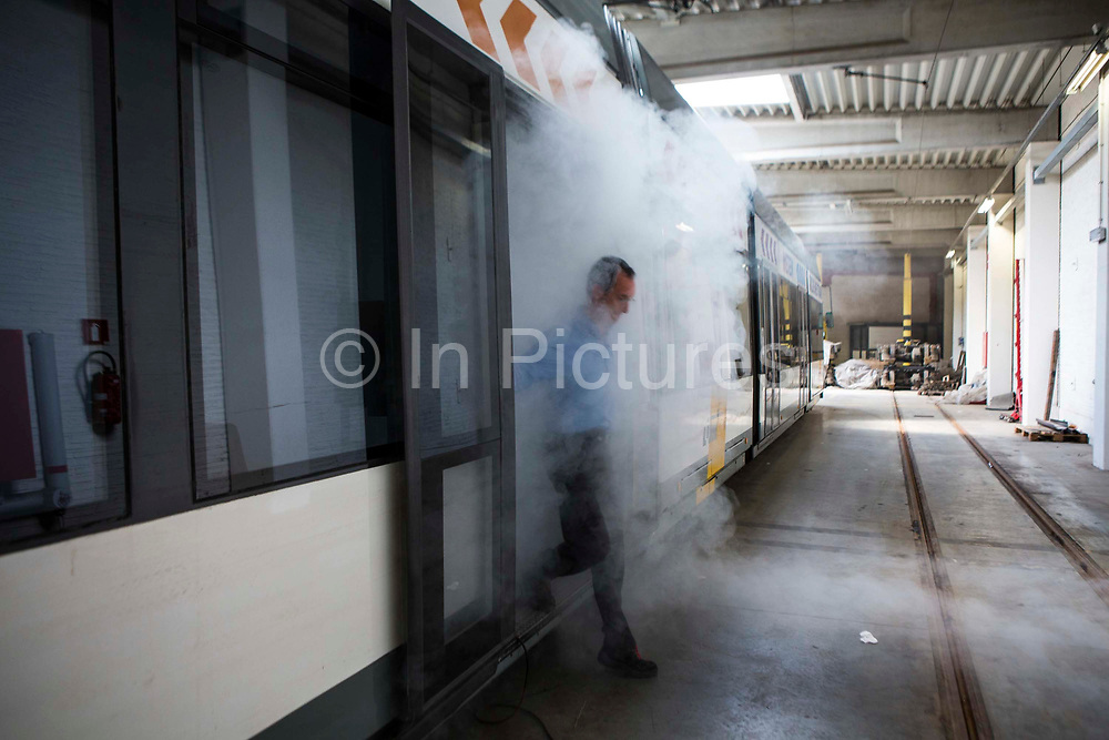 Patrick De Boeuf, Chief Executive of De Lijn, steps off an electric tram surrounded with white smoke in the tram depot in Ghent, Belgium. He is demonstrating the loss of heat from trams with a smoke machine.  He has modernized the public transport tramcars with innovative technology to reduce electricity consumption and has won a prestigious Ashden sustainable travel award for this work.