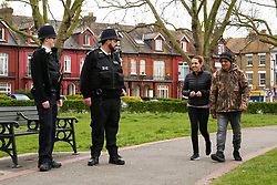 © Licensed to London News Pictures. 03/04/2020. London, UK. Police officers speak with a couple in Duckett's Common as they patrol Wood Green High Road in north London. The Government has ordered that people should go out only for food and health reasons or for work, and keep 2 meters away from other people at all times to slow the spread of the virus and reduce pressure on the NHS. Photo credit: Dinendra Haria/LNP