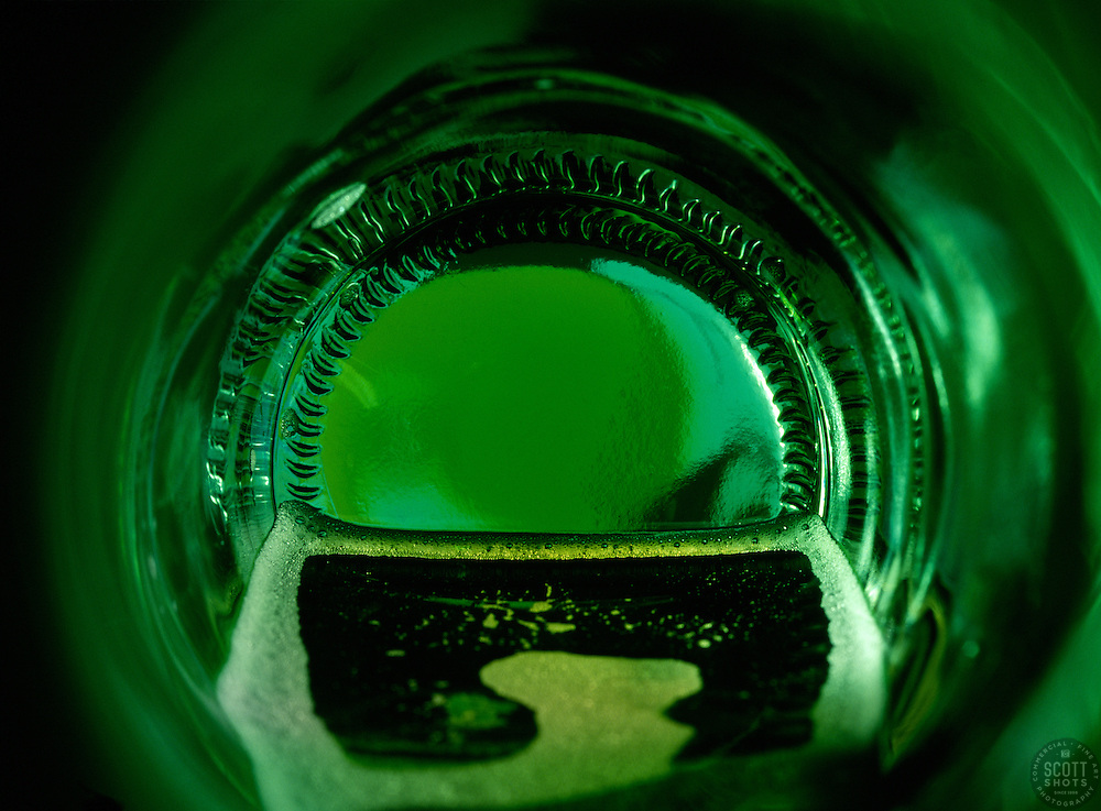 """""""Beauty at the Bottom: Lucky Night""""- This image is a photograph of a beer bottle shot right down the mouth of the bottle. A television provides the main light source."""