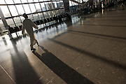 Passengers walk through late sunlight that floods through large windows in departures concourse at Heathrow Airport's T5