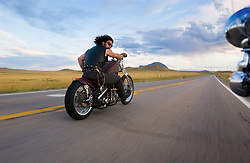 Looking Back. Paul Cox north of Bear Butte. Sturgis, SD. 2003<br /> <br /> Limited Edition Print from an edition of 50. Photo ©2003 Michael Lichter.<br /> <br /> Description: Hair flying in the wind, leather and brass, knives and power… Looking back in time to the bandits, pirates, vikings and marauders that crossed the land before.