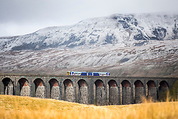 © Licensed to London News Pictures. 16/04/2016. Ribblehead UK. Picture shows a train crossing the Ribblehead Viaduct in the shadow of the snow capped Whernside mountain this morning after last night's snow fall in the Yorkshire Dales. Photo credit: Andrew McCaren/LNP