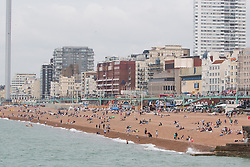 © Licensed to London News Pictures. 17/07/2016. Brighton, UK. Members of the public don't let the cloudy and grey skies stop them from spending time on the beach in Brighton. Photo credit: Hugo Michiels/LNP