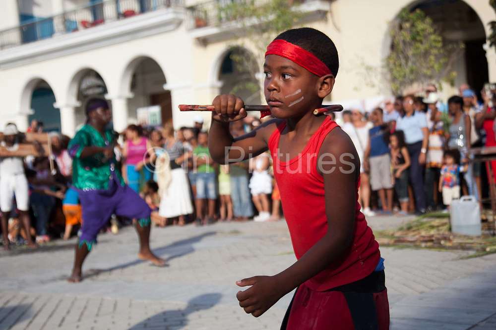 Cuban young man boy of African descent dancing, and waving a stick as part of a performance. Performance in Havana old town, local dance and theatre group enacting the slave trade, colonial rule and how African religion and beliefs continuing, becoming what is now Santeria.
